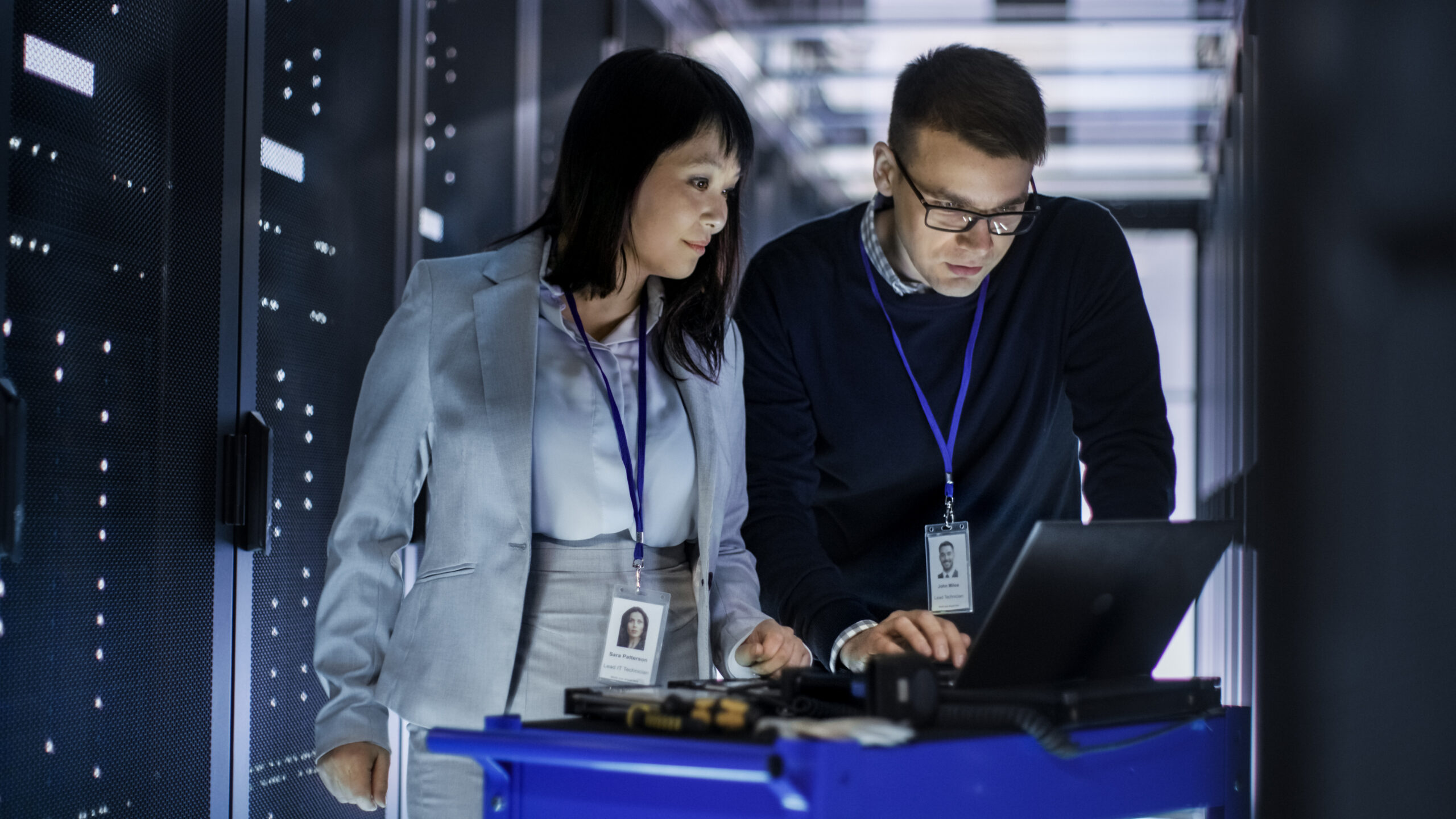 Caucasian Male and Asian Female IT Technicians Working with Computer Crash Cart in Big Data Center full of Rack Servers.